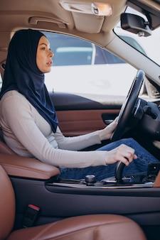 Jeune femme musulmane assise dans sa voiture et regardant dans le miroir