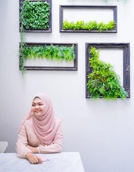 Jeune femme musulmane assise sur une salle moderne avec cadre photo.