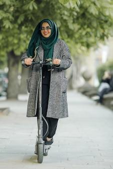 Jeune femme musulmane conduisant un scooter dans une rue