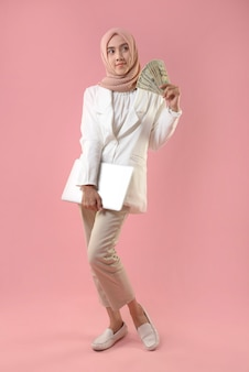 Jeune femme musulmane détient de l'argent et un ordinateur portable