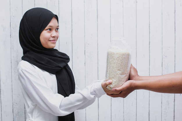 Jeune femme musulmane donnant du riz pour la zakat fitrah comme obligation pendant le mois sacré du ramadan