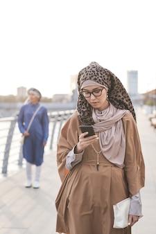 Jeune femme musulmane envoyant un message sur son téléphone portable en marchant dans la ville