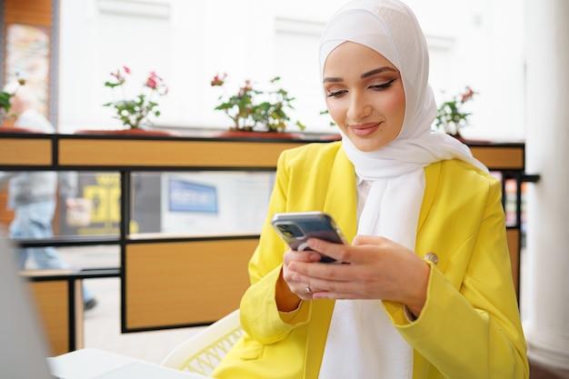Jeune femme musulmane en hijab à l'aide de son smartphone au café