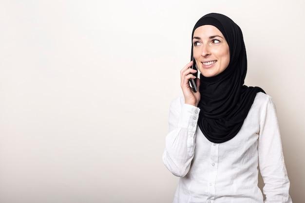 Jeune femme musulmane en hijab parlant au téléphone et regardant sur le côté