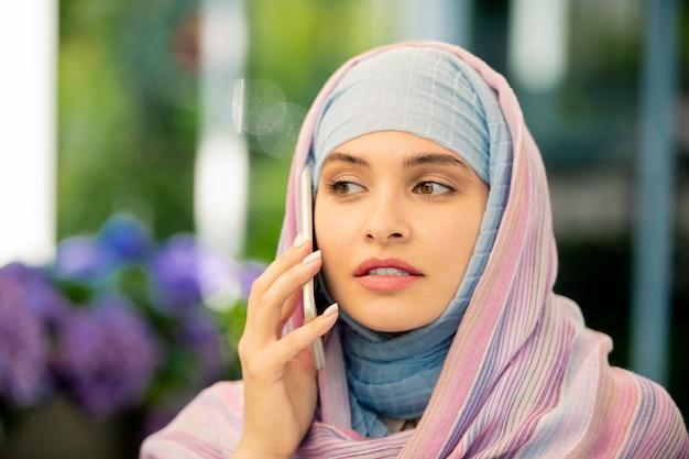 Jeune femme musulmane en hijab, parler sur smartphone à l'extérieur tout en consultant un client ou un collègue