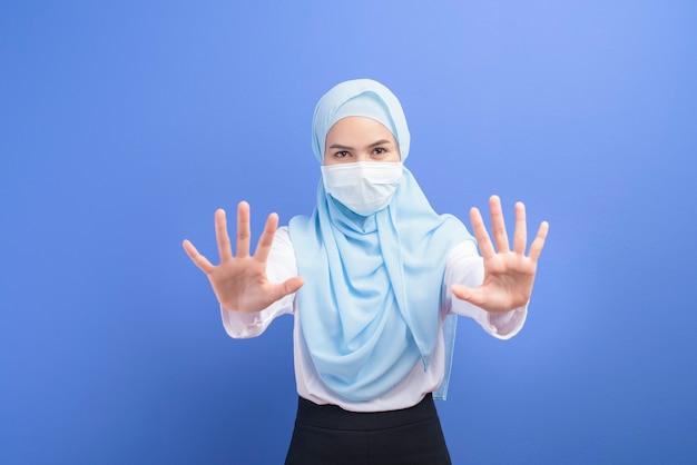Une jeune femme musulmane avec hijab portant un masque chirurgical sur bleu