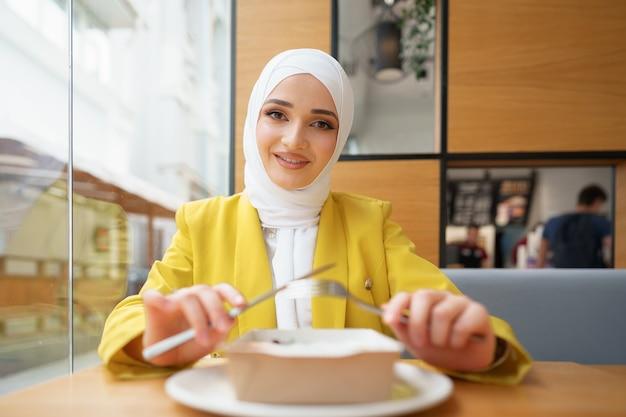 Jeune femme musulmane en hijab en train de déjeuner au café