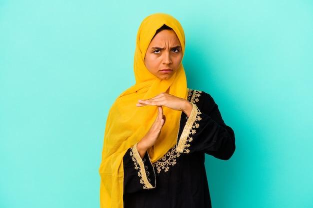 Jeune femme musulmane isolée sur fond bleu montrant un geste de délai d'attente.
