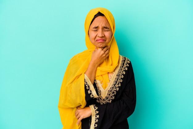 Une jeune femme musulmane isolée sur un mur bleu souffre de douleurs dans la gorge en raison d'un virus ou d'une infection.