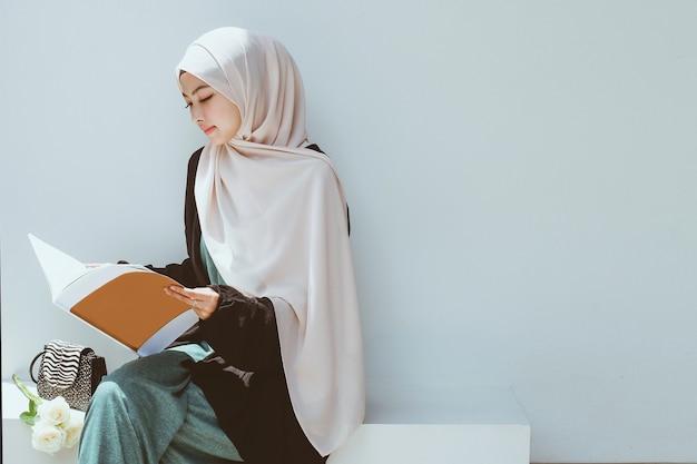 Jeune femme musulmane lisant un livre