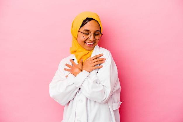 Jeune femme musulmane médecin isolée sur fond rose câlins, souriante insouciante et heureuse.