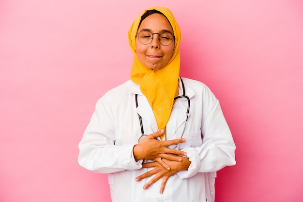 Une jeune femme musulmane médecin isolée sur fond rose touche le ventre, sourit doucement, mange et satisfait le concept.