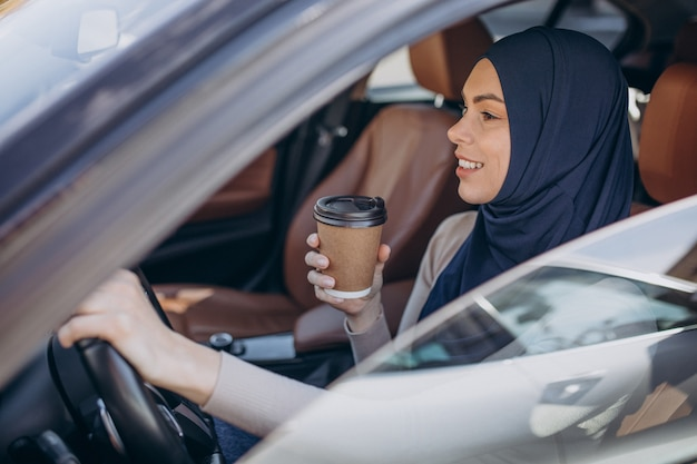 Jeune femme musulmane moderne buvant du café en voiture