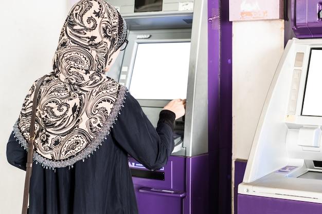 Jeune femme musulmane portant le hijab retirer de l'argent du guichet automatique.