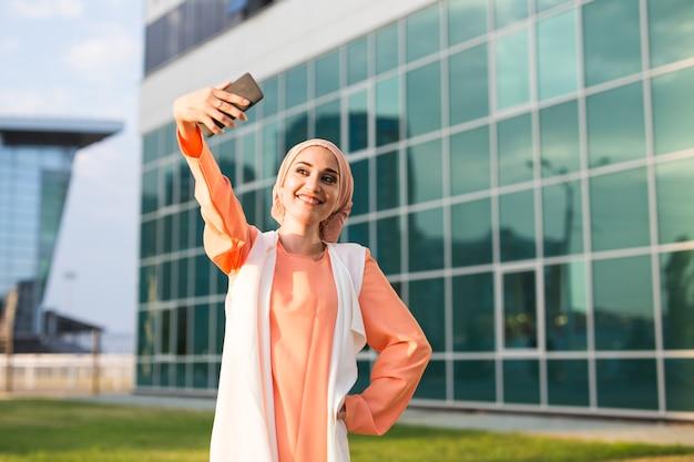 Une jeune femme musulmane prend un autoportrait