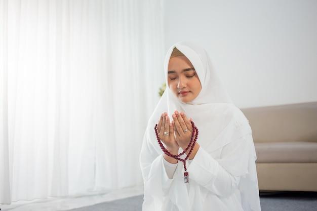 Jeune femme musulmane priant en vêtements traditionnels blancs