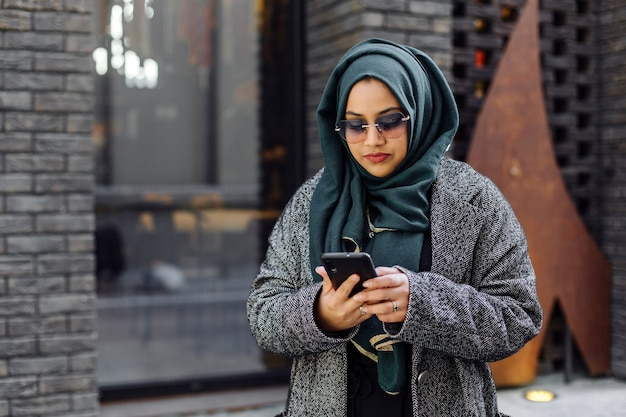 Jeune femme musulmane regardant dans un smartphone