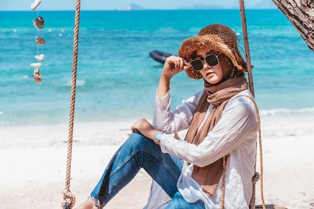Jeune femme musulmane en robe blanche, assise sur la plage en jour de vacances. heure d'été.