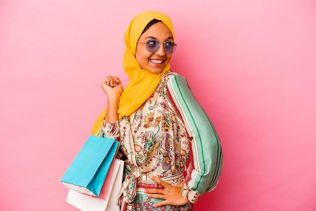 Jeune femme musulmane shopping quelques vêtements isolés sur un mur rose regarde de côté souriant, gai et agréable