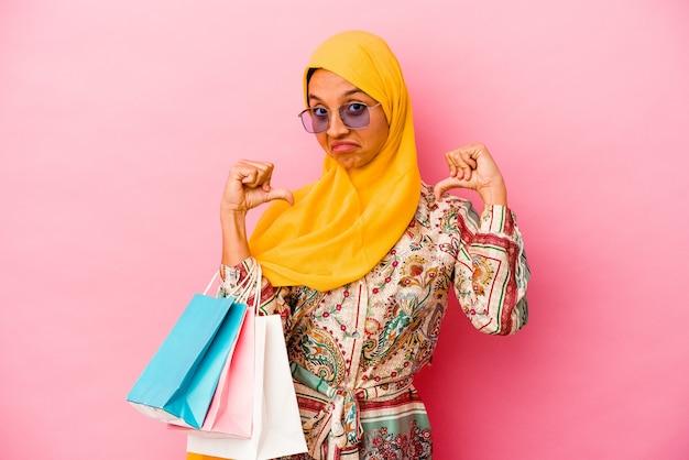 Jeune femme musulmane shopping quelques vêtements isolés sur un mur rose se sent fier et confiant, exemple à suivre