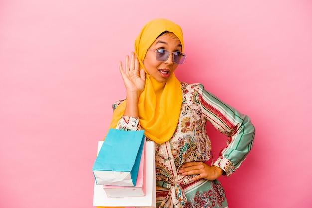 Jeune femme musulmane shopping des vêtements isolés sur un mur rose en essayant d'écouter un potin