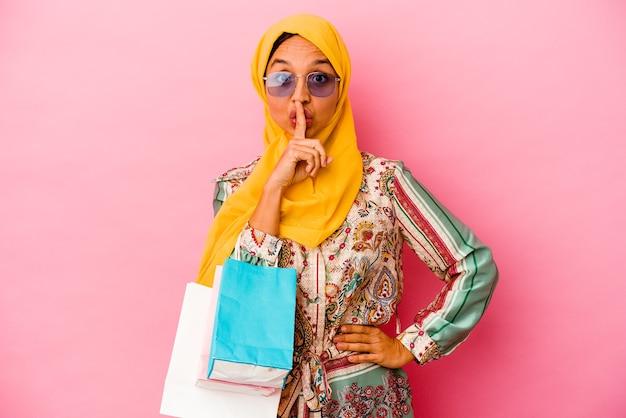 Jeune femme musulmane shopping des vêtements isolés sur un mur rose en gardant un secret ou en demandant le silence