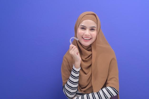 Une jeune femme musulmane tenant des accolades invisalign en studio, soins dentaires et concept orthodontique.