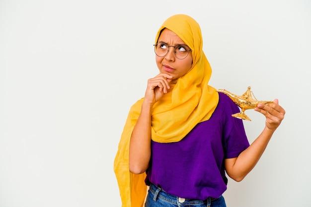Jeune femme musulmane tenant une lampe isolée sur un mur blanc à la recherche de côté avec une expression douteuse et sceptique