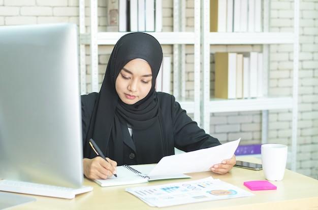 Jeune femme musulmane travaille au bureau à l'aide de téléphone