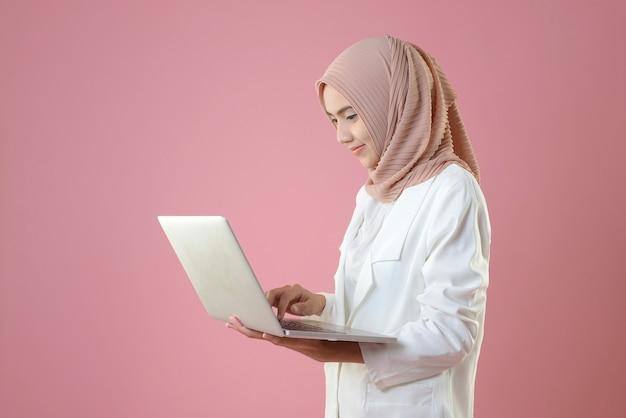 Jeune femme musulmane travaille en ligne par ordinateur portable