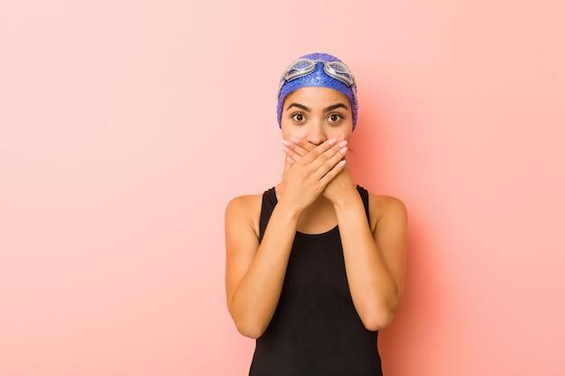 Jeune femme nageuse arabe isolée choquée couvrant la bouche avec les mains.