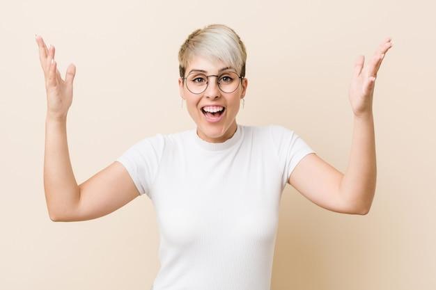 Jeune femme naturelle authentique vêtue d'une chemise blanche recevant une agréable surprise, excitée et levant les mains.