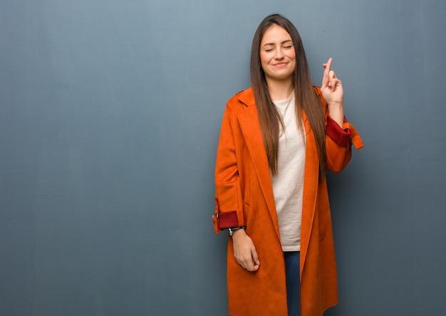 Jeune femme naturelle croise les doigts pour avoir de la chance