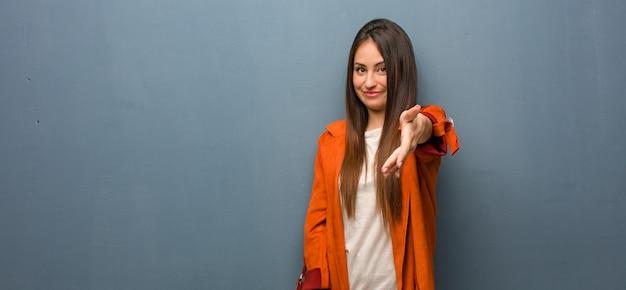 Jeune femme naturelle tendre la main pour saluer quelqu'un