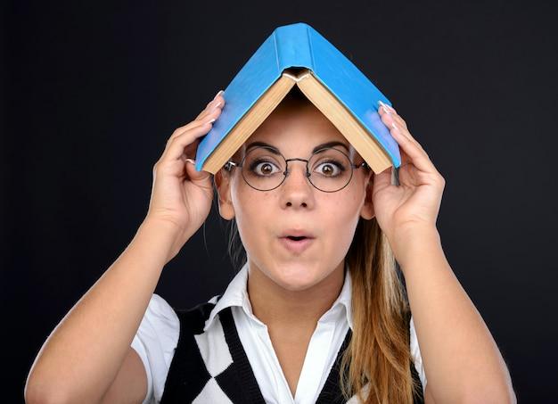 Jeune femme nerd expression folle dans des verres avec un livre sur la tête