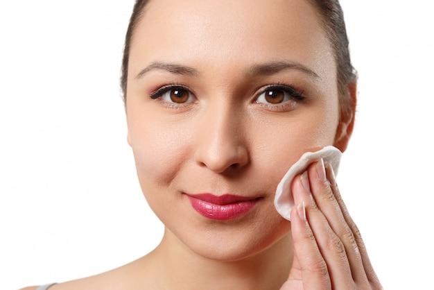 Une jeune femme nettoie son visage avec un coton. isolé