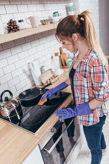 Jeune femme de nettoyage du four à la cuisine à la maison essuyage à la main de la cuisinière et des couvercles de brûleur.