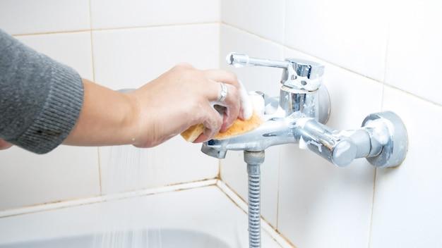 Jeune femme nettoyant et lavant le robinet ou le robinet d'eau de la salle de bain avec une éponge et de la mousse.