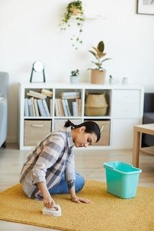 Jeune femme nettoyant le tapis avec une brosse dans le salon à la maison
