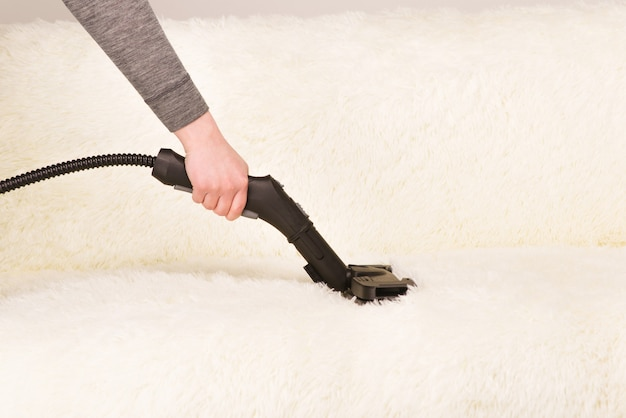 Jeune femme avec un nettoyeur vapeur nettoie le tapis sur le canapé