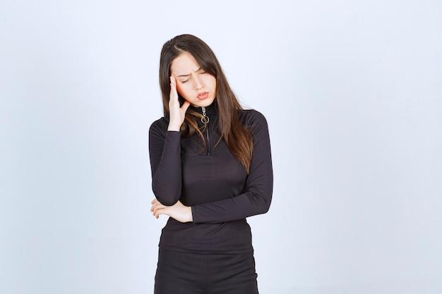 Jeune femme en noir pensant et essayant de comprendre