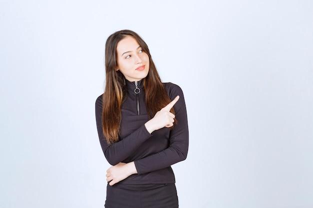 Jeune femme en noir pointant vers le côté droit
