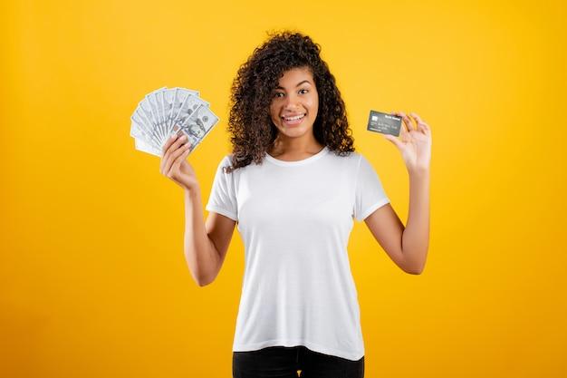 Jeune femme noire africaine avec dollars en argent et carte de crédit en main isolé sur jaune