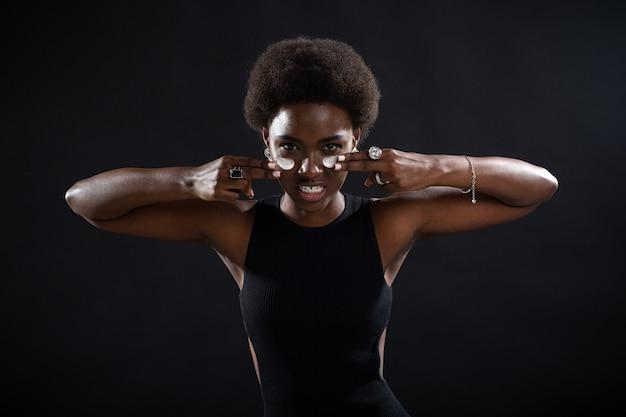 Jeune femme noire afro-américaine appliquant par les doigts un frottis de crème blanche sur son visage avec émotion