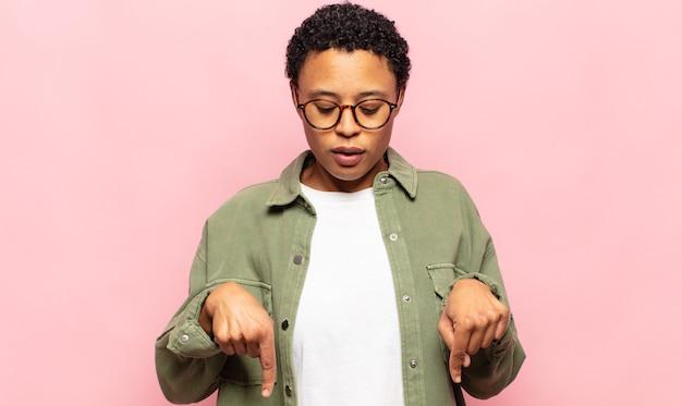 Jeune femme noire afro avec la bouche ouverte pointant vers le bas avec les deux mains, l'air choquée, étonnée et surprise