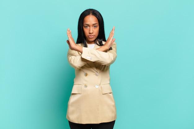 Jeune femme noire à l'air agacée et malade de votre attitude, en dire assez! les mains croisées devant vous disant d'arrêter. concept d'entreprise
