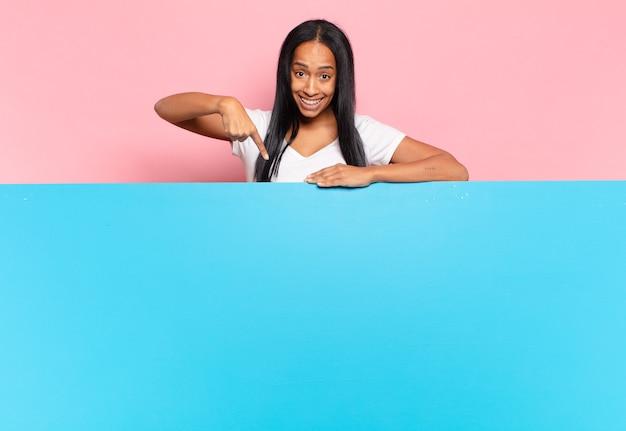 Jeune femme noire à l'air excitée et surprise pointant vers le côté et vers le haut pour copier l'espace. concept d'espace de copie