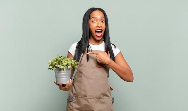 Jeune femme noire à l'air excitée et surprise pointant vers le côté et vers le haut pour copier l'espace. concept de jardinier