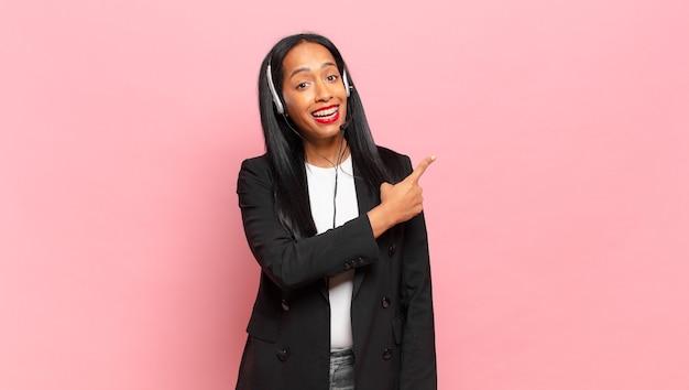 Jeune femme noire à l'air excitée et surprise pointant vers le côté et vers le haut pour copier l'espace. concept de télémarketing