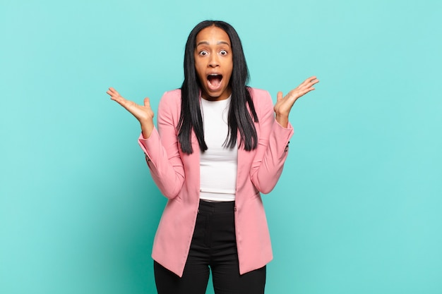Jeune femme noire à l'air heureuse et excitée, choquée par une surprise inattendue avec les deux mains ouvertes à côté du visage